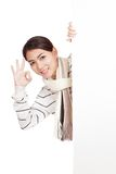 Asian girl with scarf peeking from behind blank sign show OK Stock Photography