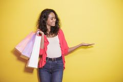 Asian girl with shopping bag presenting copy space. Portrait of asian girl with shopping bag presenting copy space on yellow background Stock Photography