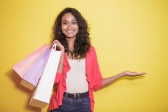 Asian girl with shopping bag presenting copy space. Portrait of asian girl with shopping bag presenting copy space on yellow background Stock Image