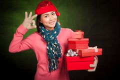 Asian girl  show OK with red christmas hat and gift boxes Royalty Free Stock Images