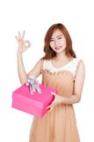 Asian girl show Ok sign with a gift box Royalty Free Stock Photography