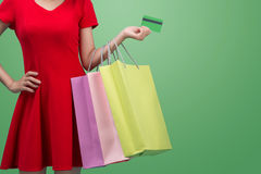 Asian girl showing credit card in hand, over blue background Stock Photos