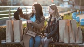 Asian girl showing latest purchase to her friend stock footage