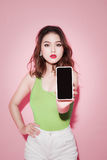 Asian girl showing smartphone screen on pink background. Stock Photos
