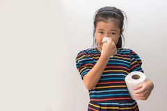 Asian girl sick with sneezing on nose and cold cough on tissue paper.  stock image
