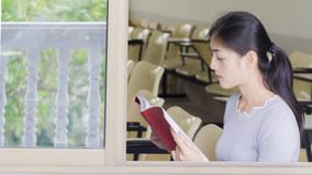 The asian girl reads a red book Stock Photo