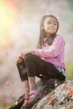 Asian girl sit and relax with Sakura fall Stock Photography