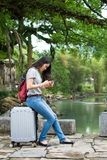 Girl siting on the suitcase and playing her phone in the stunnin royalty free stock image