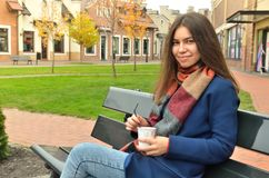 Asian girl sits on a bench outdoor with a cup of coffee. In her hands. Smiles and looks at the photographer. Dressed in a coat and a scarf. Hair split Stock Photography