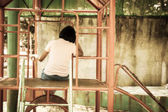 Asian girl sitting alone at playground Stock Images