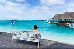 Asian girl sitting in chair watching the sea Stock Image