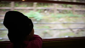 Asian girl sitting in the dark looking out window. While travel by Sagano Romantic Train, Japan stock video