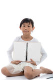 Asian girl sitting and holding blank notebook. On white background Royalty Free Stock Images