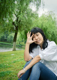 Asian girl sitting on the lawn Stock Photography