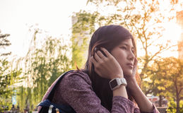 Asian girl is sitting in the park. In front of bright sun Royalty Free Stock Photo