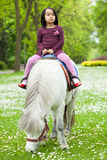 Asian girl sitting on pony. View of asian girl sitting on pony Stock Photo