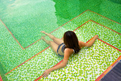 Asian girl sitting in the private swimming pool. Back of Asian girl in black bikinis sits in swimming pool with green mosaic tile at the bottom Royalty Free Stock Image