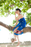 Asian girl sitting on tree trunk Royalty Free Stock Photography