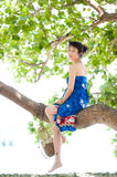 Asian girl sitting on tree trunk Royalty Free Stock Photo