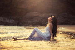 Asian girl sitting on a tropical beach by the sea to enjoy the s stock photos
