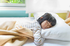 Asian girl sleeping on bed covered with blanket. Stock Photos