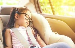 Girl sleeping in child car seat.