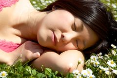 Asian girl sleeping in park surrounded by flowers Royalty Free Stock Images