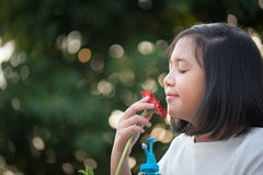 Asian girl is smelling the daisy flower outdoors Royalty Free Stock Photo