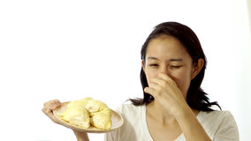 Asian girl smelling stinky durian. Smelly fruit of tropical area Stock Photo