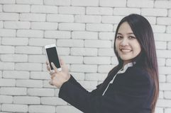 Asian girl smiles and uses her hand to point smartphone, background white brick wall, Online Trading Concepts and Auctions stock images