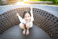 Asian girl smiling happily sitting on a big chair by the pool on holiday stock photography