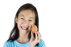Asian girl smiling and holding an egg stock photography
