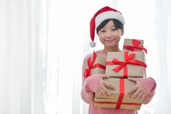 Asian girl smiling and holding stack of gift boxes. Stock Image