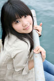 Asian girl smiling looking up. Asian girl smiling holding onto railing Stock Photos