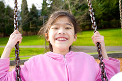 Asian girl smiling on a swing at the park. Happy little nine year old part Asian girl smiling on a swing at the park Stock Photos
