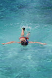 Asian girl snorkeling in crystal clear water Royalty Free Stock Photos