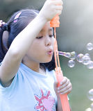 Asian girl and soap sud. A chinese girl blowing soap sud in a park Royalty Free Stock Photos