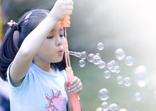 Asian girl and soap sud. A chinese girl blowing soap sud in a park Stock Photos