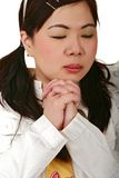 Asian Girl Solemnly Praying. Asian girl in casual dress closing her eyes and solemnly praying Stock Photo