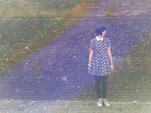 Asian girl stand alone in front of old brick wall background Royalty Free Stock Photography