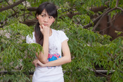 Asian girl standing amongst leaves Royalty Free Stock Images