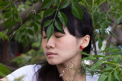 Asian girl standing amongst leaves Stock Image