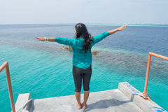 Asian Girl Standing At The Top Facing Ocean And Rising Hands Stock Photo