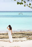 Asian girl standing on beach watching towards Royalty Free Stock Images