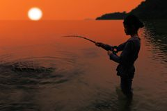 Asian girl standing and fishing with rod and reel in the sea nea Stock Photo