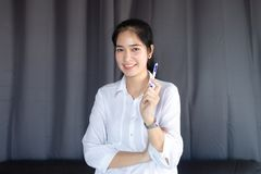 Asian girl standing holding pen and smiling happily stock photography
