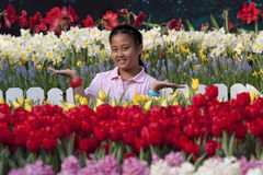 Asian girl standing in tulip flower field Stock Photo