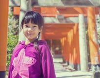 An Asian girl standing under Tori Entrance of Sumiyoshi Shrine. Royalty Free Stock Image