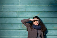 Asian girl is standing by the wall and screwing up her eyes. Because of the bright sun. She smiles and tries to cover her face with her hand Royalty Free Stock Images