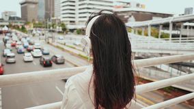 An Asian girl stands on a bridge over traffic and in white headphones listens to music. stock video